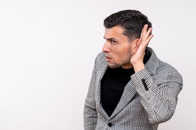 Vista frontal do homem bonito de terno ouvindo algo em pé sobre um fundo branco isolado