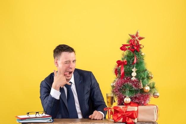 Vista frontal do homem bonito piscando para a câmera, sentado à mesa perto da árvore de natal e presentes em amarelo