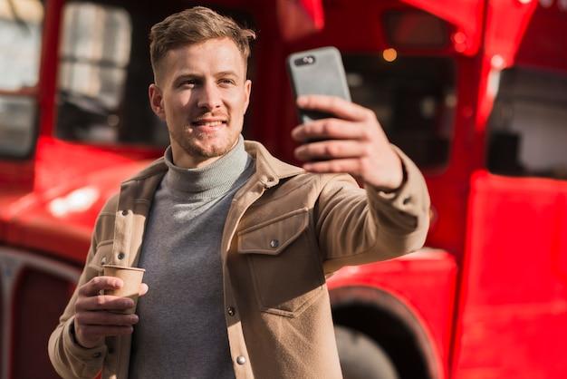 Vista frontal do homem bonito, tomando uma selfie