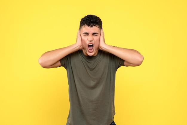 Vista frontal do homem cobre seus ouvidos com as mãos e grita