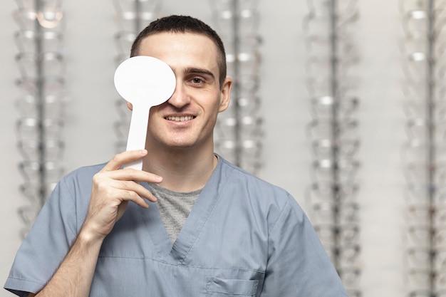 Vista frontal do homem cobrindo o olho para o teste de visão