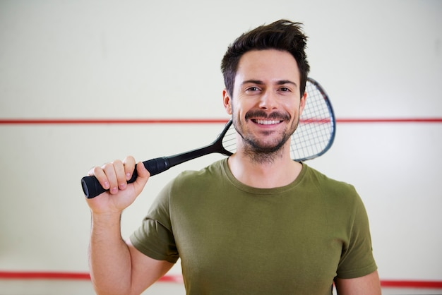 Vista frontal do homem com a raquete antes do jogo de squash