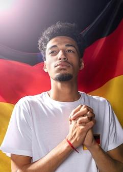 Vista frontal do homem com bandeira alemã