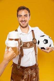 Vista frontal do homem com bola e cerveja pint