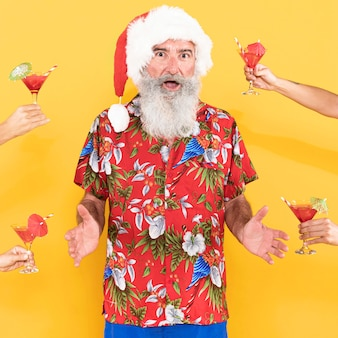 Vista frontal do homem com camisa tropical e chapéu de natal