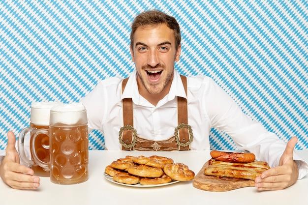 Vista frontal do homem com comida alemã e cerveja