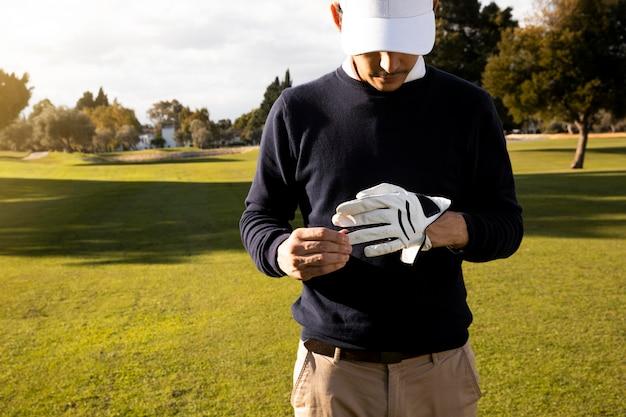 Vista frontal do homem com luva de golfe