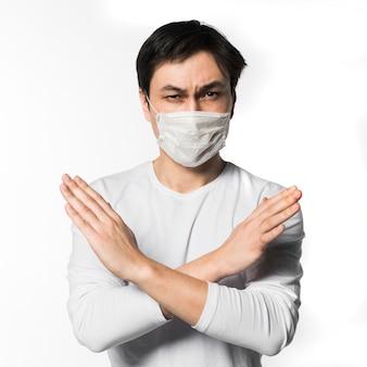 Vista frontal do homem com máscara médica, fazendo x sinal com braços