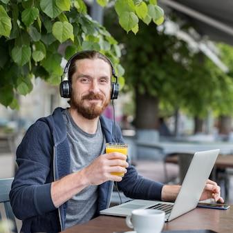Vista frontal do homem com suco em um terraço com fones de ouvido e laptop
