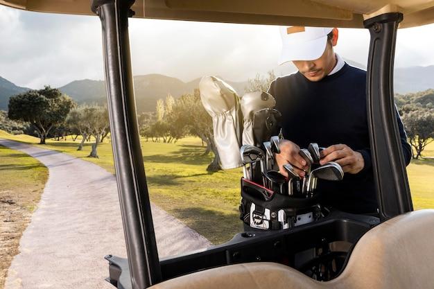 Vista frontal do homem com tacos de golfe ao lado do carrinho de golfe