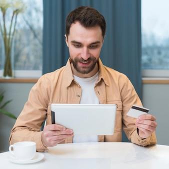 Vista frontal do homem compras on-line usando tablet e cartão de crédito