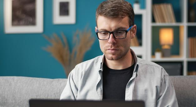 Vista frontal do homem concentrado de óculos e roupa casual usando laptop sentado no sofá no apartamento