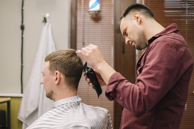 Vista frontal do homem cortando o cabelo