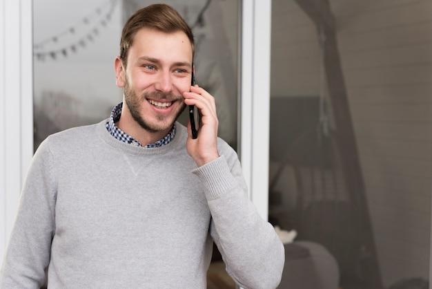 Vista frontal do homem de camisola, falando ao telefone