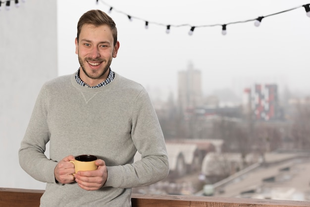 Vista frontal do homem de camisola, segurando o copo em casa