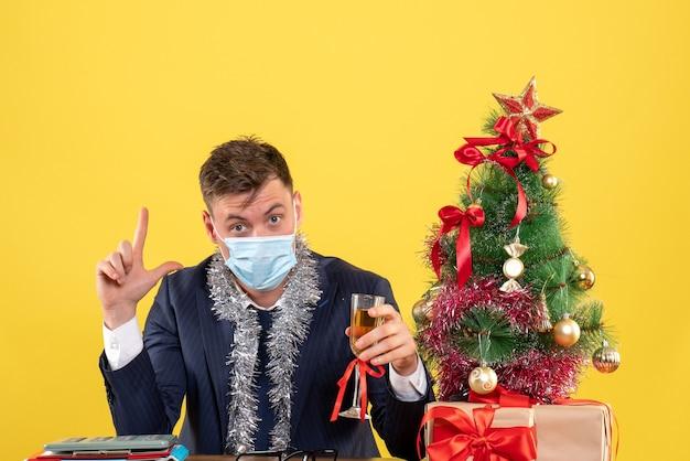 Vista frontal do homem de negócios com máscara brindando, sentado à mesa perto da árvore de natal e presentes em amarelo