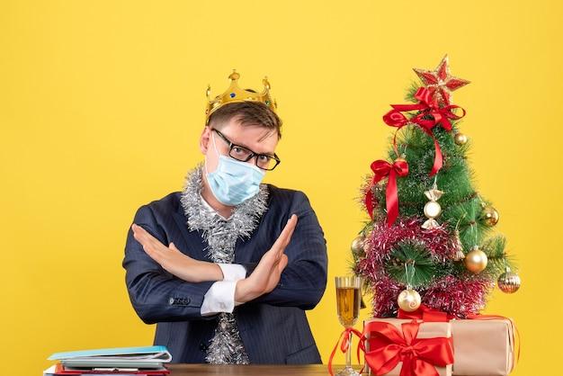 Vista frontal do homem de negócios cruzando as mãos, sentado à mesa perto da árvore de natal e presentes na parede amarela