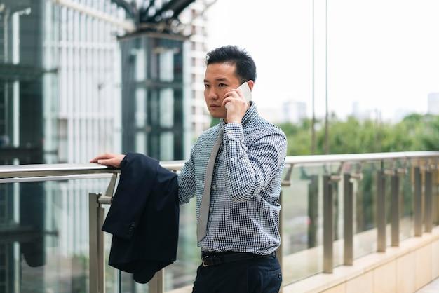 Vista frontal do homem de negócios falando ao telefone