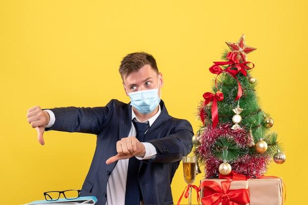Vista frontal do homem de negócios fazendo sinal de polegar para baixo sentado à mesa perto da árvore de natal e presentes em amarelo