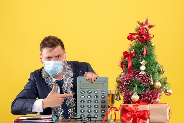 Vista frontal do homem de negócios, mostrando a calculadora sentada à mesa perto da árvore de natal e presentes em amarelo