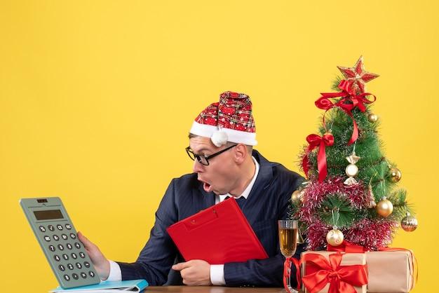 Vista frontal do homem de negócios olhando para a calculadora segurando a prancheta, sentado à mesa perto da árvore de natal e presentes em amarelo