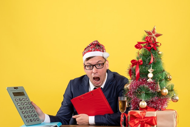 Vista frontal do homem de negócios, segurando a calculadora, sentado à mesa perto da árvore de natal e presentes em amarelo.