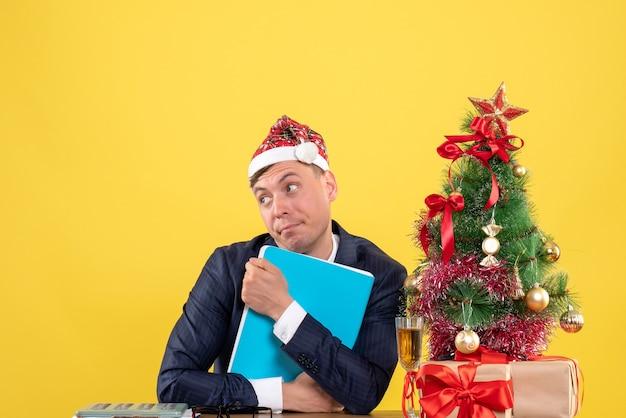 Vista frontal do homem de negócios segurando firme seus documentos, sentado à mesa perto da árvore de natal e presentes em amarelo