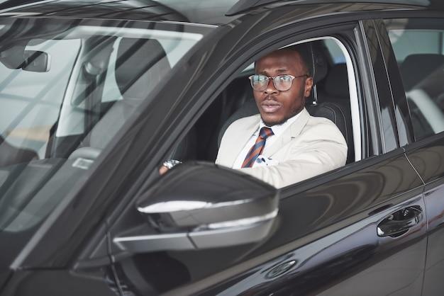 Vista frontal do homem de negócios sério bonito africano elegante dirige um carro.