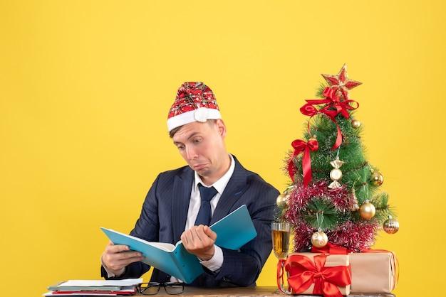 Vista frontal do homem de negócios verificando documentos, sentado à mesa perto da árvore de natal e presentes na parede amarela