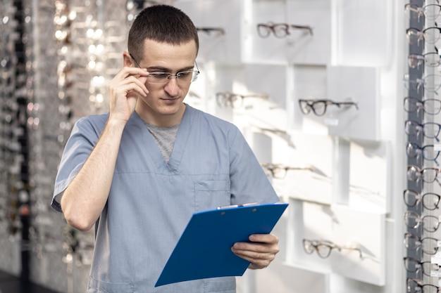 Vista frontal do homem de óculos e olhando para o bloco de notas