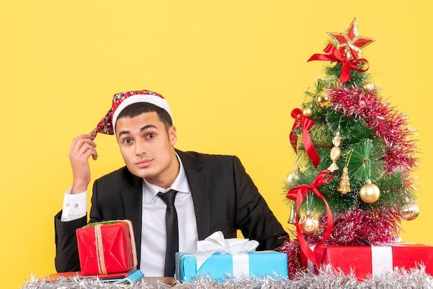 Vista frontal do homem de terno com chapéu de papai noel sentado à mesa árvore de natal e presentes
