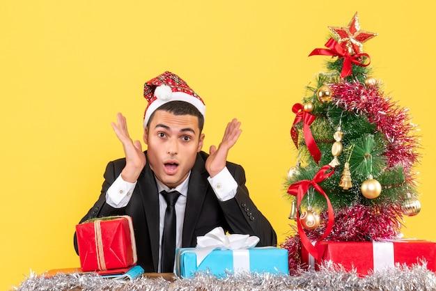 Vista frontal do homem de terno com chapéu de papai noel sentado na mesa árvore de natal e presentes