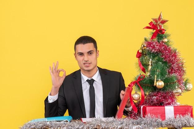 Vista frontal do homem de terno sentado à mesa segurando o documento, fazendo okey assinar a árvore de natal e presentes