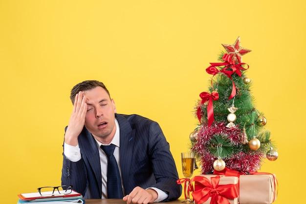 Vista frontal do homem decepcionado, segurando sua cabeça, sentado à mesa perto da árvore de natal e presentes em amarelo.