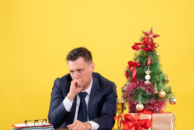 Vista frontal do homem decepcionado sentado à mesa perto da árvore de natal e presentes em amarelo.