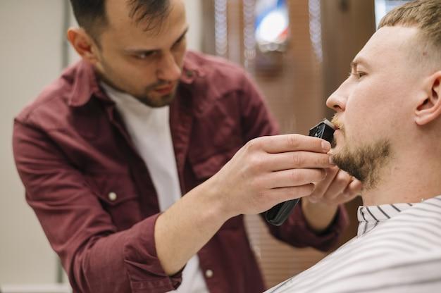 Vista frontal do homem depilar a barba