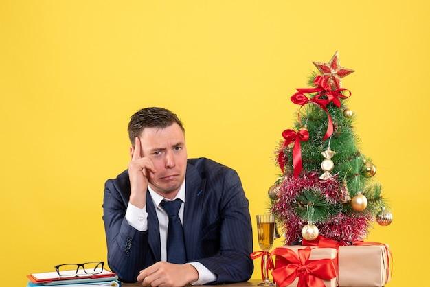 Vista frontal do homem deprimido, sentado à mesa perto da árvore de natal e presentes em amarelo.