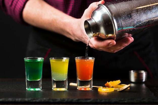 Vista frontal do homem derramando cocktail em copos de shot