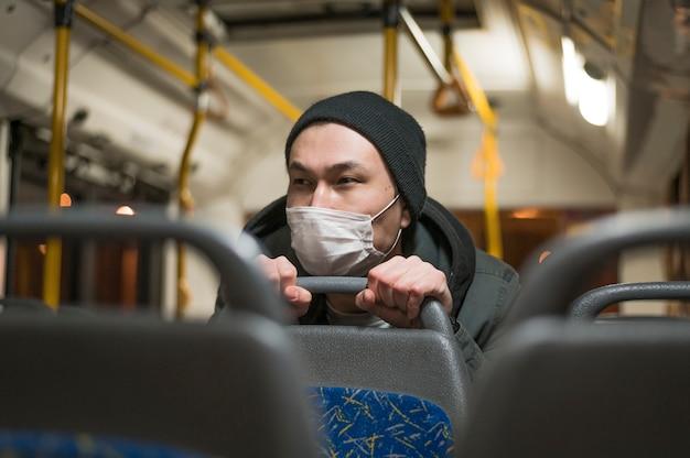 Vista frontal do homem doente, andando de ônibus