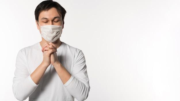 Vista frontal do homem doente com máscara médica rezando