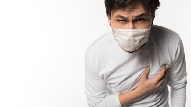 Vista frontal do homem doente tocando seu peito com dor