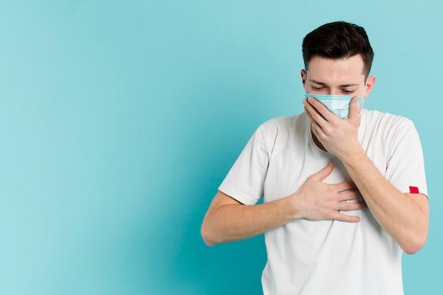 Vista frontal do homem doente, tossindo enquanto usava uma máscara médica