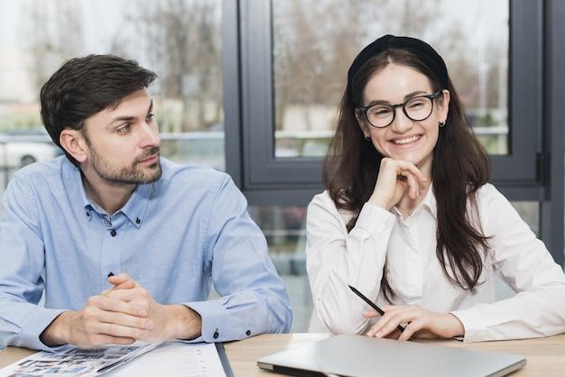 Vista frontal do homem e da mulher a participar de uma entrevista de emprego