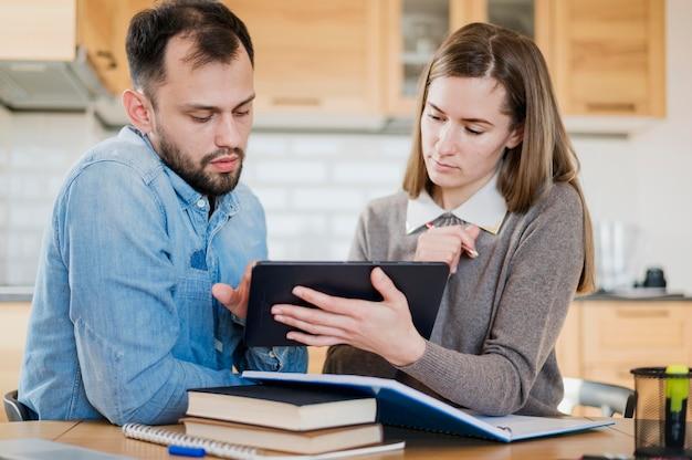 Vista frontal do homem e da mulher aprendendo em casa do tablet