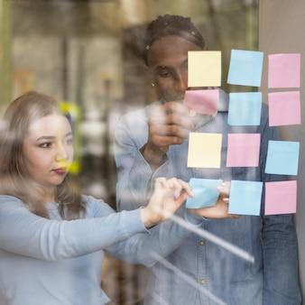 Vista frontal do homem e da mulher colocando notas auto-adesivas na janela do escritório