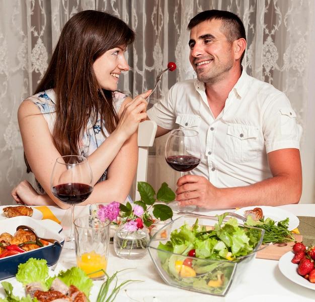 Vista frontal do homem e da mulher na mesa de jantar com vinho e comida
