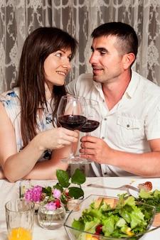 Vista frontal do homem e da mulher na mesa de jantar com vinho