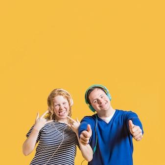 Vista frontal do homem e mulher ouvindo música em fones de ouvido com espaço de cópia