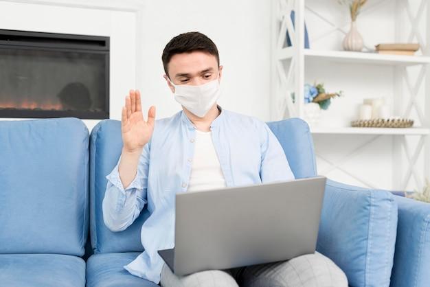 Vista frontal do homem em casa com máscara médica trabalhando no laptop