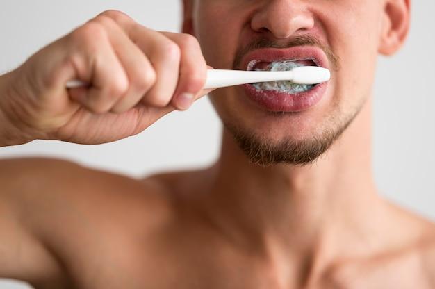 Vista frontal do homem escovando os dentes